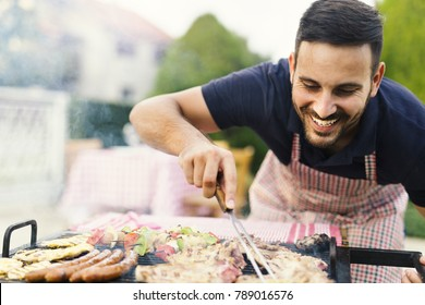 Smiling man checking meat on the grill