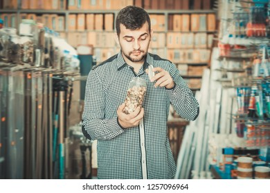 Smiling man choosing new DIY details in houseware store