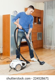Smiling man  cleaning with vacuum cleaner on parquet floor in living room