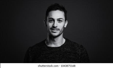 Smiling man close up portrait against dark grey background. Black and white image.