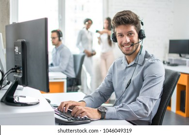 Smiling man customer support phone operator with headset working in call center.