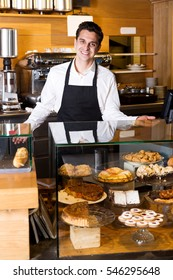 Smiling man with delicious cream pies at bakery display