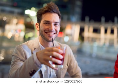 Smiling man drinking a cocktail