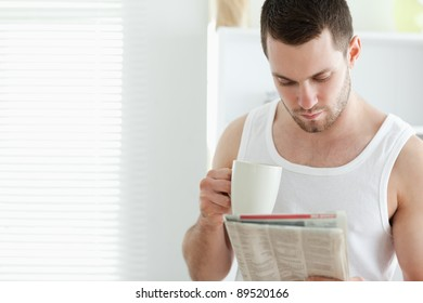 Smiling man drinking coffee while reading the news in his kitchen