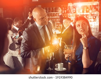 Smiling man enjoying conversation with young female colleague on corporate party in bar