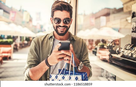 Smiling man enjoying in shopping. Consumerism, lifestyle concept