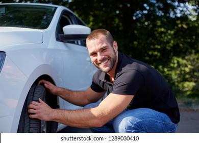 Smiling man examining tires at his new car