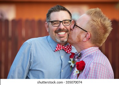 Smiling man with eyeglasses being kissed by spouse