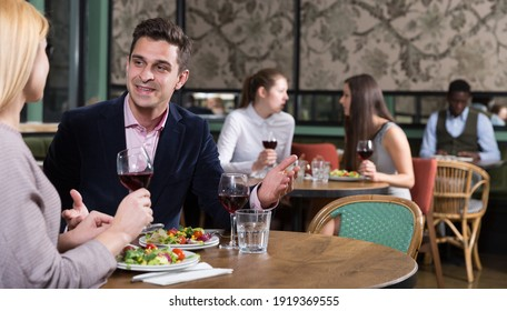 Smiling man with female colleague on friendly meeting over dinner with wine in restaurant