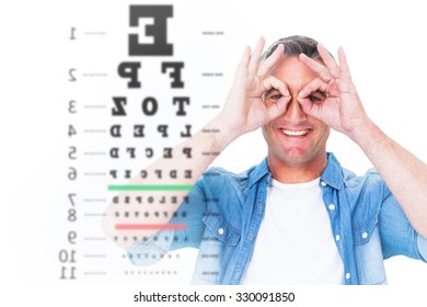 Smiling man with fingers around his eyes against eye test
