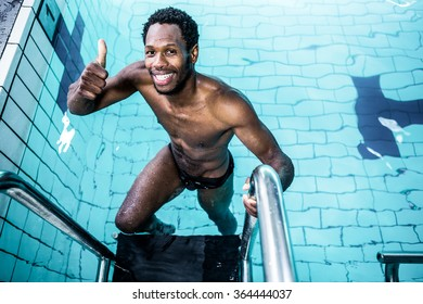 Smiling man getting out the pool with thumbs up