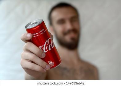 Smiling man gives non-alcoholic Coca-Cola aluminium tin can in garage interior