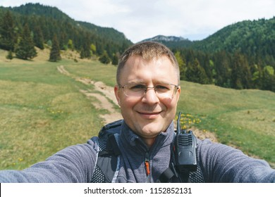 smiling man in glasses making selfie with great view