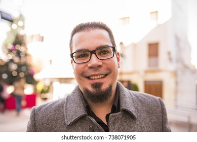 Smiling man with goatee in outdoors image with elegant suit and glasses