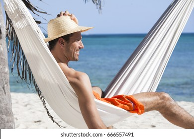 smiling man in a hammock on the beach