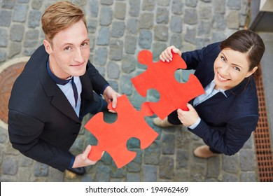 Smiling man and happy woman holding big red jigsaw puzzle pieces
