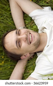 The smiling man has a rest on a grass