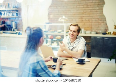 Smiling man having an interview with woman at coffee shop