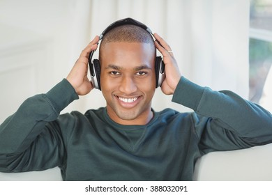 Smiling man with headphones on the sofa looking at the camera