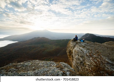 Smiling man hiker with backpack siting and relaxing on the top of the mountain and looking at beautiful yellow autumn landscape sunset over clouds