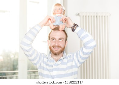 Smiling Man Holding a Doll on His Head