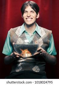 Smiling man holding fishbowl