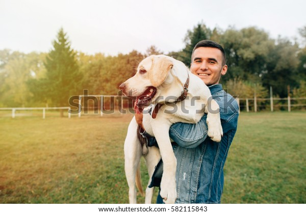 Smiling man holding his dog Labrador in hands in park
