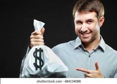 Smiling man holding money bag and winking
