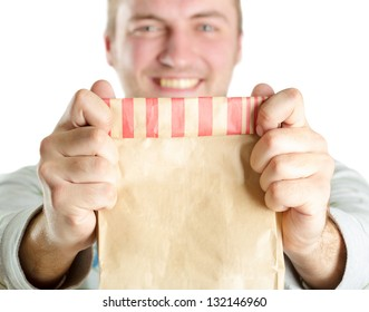 Smiling man holding out a paper bag. Isolated on white