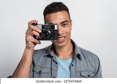 Smiling man holding a retro photocamera against his face and looking at the camera- Image