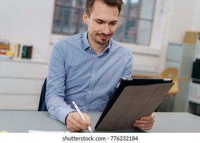Smiling man holding a stylus pen sitting looking at a digital tablet he is holding in his other hand as he sits at an office table or in a design studio