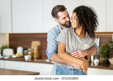 Smiling man hugging from behind charming African American woman, two people standing and joyfully looking at each other. Young international couple happily spending time in cozy modern kitchen at home