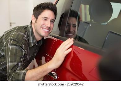 Smiling man hugging a red car at new car showroom