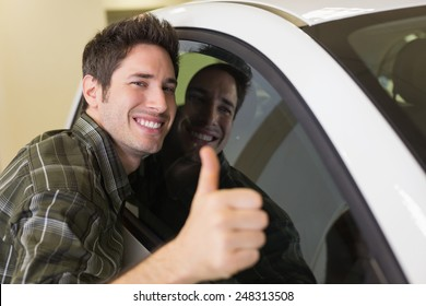 Smiling man hugging a white car while giving thumbs up at new car showroom