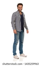 Smiling man in jeans, sneakers, glasses and unbuttoned lumberjack shirt is standing and looking at camera. Full length studio shot isolated on white.