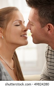 Smiling man kissing woman with eyes closed in closeup.