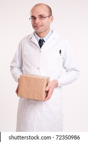 Smiling man in  a lab coat carrying a parcel