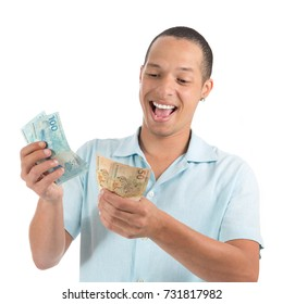 Smiling man with large volume of money. Counting banknotes of Reais do Brazil. Young latin american man wearing blue shirt. Isolated on white background.
