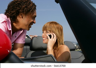 Smiling man leaning on a car near a young woman phoning