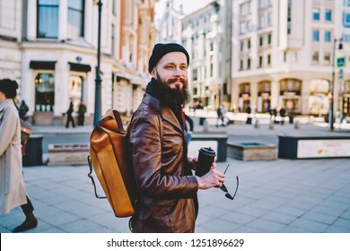 Smiling man with leather rucksack looking on showplaces during wanderlust around Moscow city, positive male tourist with coffee spending vacations in Russia walking on streets and enjoying leisure