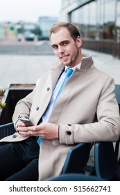 a smiling man in a light coat and tie and bag looking into the camera. Portrait of a businessman outdoor. Man holding mobile phone sitting on chair outdoor. Handsome man sitting in the chair.