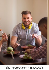 Smiling man looking at camera while his friends eating healthy vegan dishes. Happy friends spending their free time in vegan restaurant or cafe.