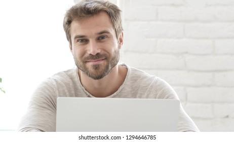 Smiling Man Looking at Camera at Work