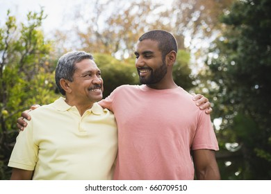 Smiling man looking at his father standing together against trees
