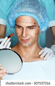 Smiling man looking in the mirror before cosmetic surgery. Doctor's hands with marker draws surgical lines on the face (forehead, eyes, nose, cheekbone and jaw).  Plastic Surgery concept