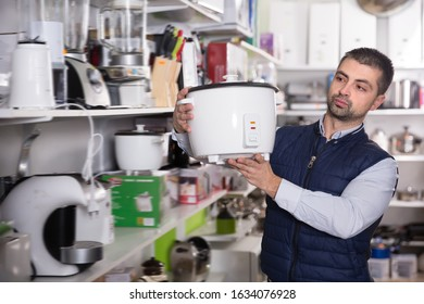 Smiling man is looking on multivariates for kitchen in store