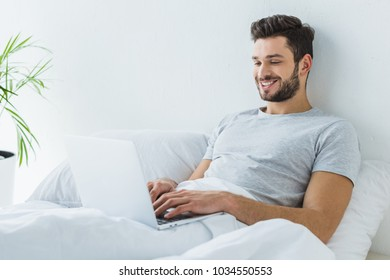 smiling man lying on bed and using laptop