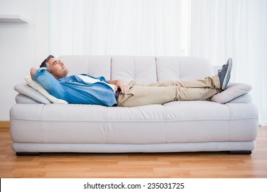 Smiling man lying and relaxing on the couch at home in the living room