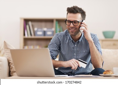 Smiling man making order by mobile phone