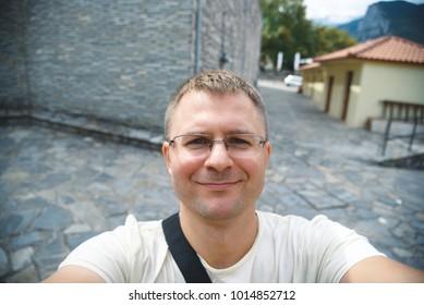 smiling man making selfie at old city